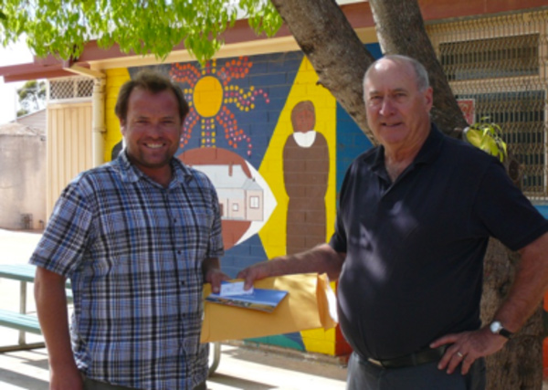 Howard Coote (right) on behalf of the EPCF presents Koonibba School Principal Wade Branford (Left) with Back to School Vouchers for his students.